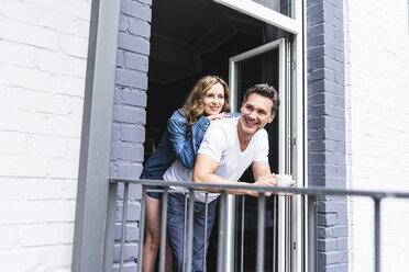 Happy couple in nightwear at home at balcony door - UUF14336