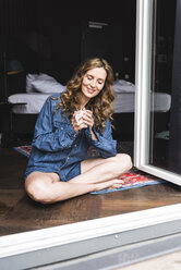 Smiling woman in denim shirt at home with cup of coffee sitting at French window - UUF14354