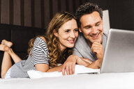Happy couple lying on bed at home looking at laptop - UUF14372