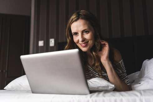 Smiling woman lying on bed at home looking at laptop - UUF14378