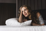 Thoughtful woman lying on bed at home looking away - UUF14381