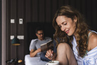 Smiling woman with cup of coffee in bedroom with man in background - UUF14387