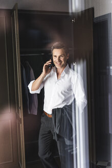 Smiling businessman on cell phone at wardrobe at home - UUF14396