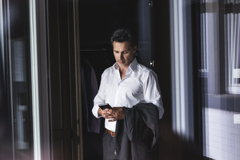 Businessman standing at wardrobe at home using cell phone - UUF14399