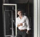 Smiling businessman with cup of coffee standing at the window at home - UUF14402