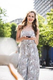 Portrait of smiling woman with cell phone in the city - UUF14405