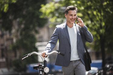 Smiling man on cell phone pushing bike in the city - UUF14417