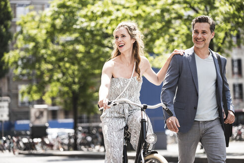 Happy couple with bicycle in the city - UUF14420