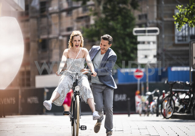 Happy carefree couple with bicycle in the city - UUF14423 - Uwe Umstätter/Westend61