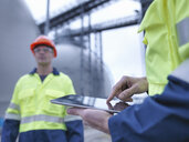 Workers using digital tablet at biomass facility, close up - CUF38924