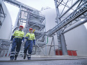 Workers walking through biomass facility, low angle view - CUF38927