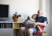 Girl sitting on grandfathers lap in living room playing hand held computer game - CUF39136