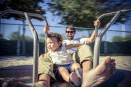 Father and toddler daughter spinning on park roundabout - ISF16472