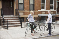 Young couple with bicycles chatting on street - ISF16484
