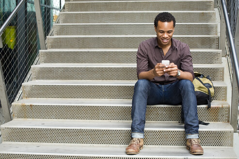 Young man texting on smartphone on city stairway - ISF16490