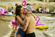Greece, Crete, passionate lovers kissing at beach party - BEF00179