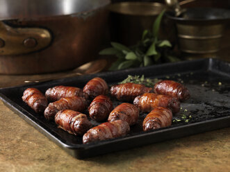 Christmas dinner snack. Festive spiced bacon and venison cocktail sausage rolls. Pigs in blankets with thyme bay leaves - CUF39338