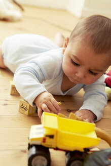 Baby lying on front playing with blocks and truck - CUF39374