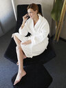 Young woman in bathrobe on mobile phone in hotel room - CUF39404