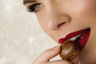 Cropped image of young woman eating chocolate - CUF39455