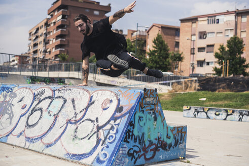 Tattooed man doing parkour in a skatepark - ACPF00082
