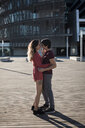 Affectionate young couple standing on city square - MAUF01449