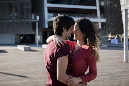 Affectionate young couple standing on city square - MAUF01452