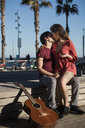 Spain, Barcelona, affectionate couple with a guitar sitting on a bench at seaside promenade - MAUF01458