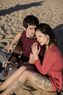 Affectionate couple with a guitar sitting on the beach - MAUF01461