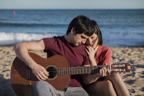 Couple with a guitar sitting on the beach - MAUF01464