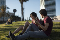 Spain, Barcelona, young man playing guitar for girlfriend sitting on a meadow - MAUF01470