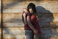 Affectionate young couple hugging at wooden wall - MAUF01476