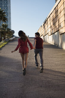 Spain, Barcelona, couple running hand in hand  in the city - MAUF01479