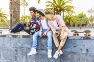 Three friends sitting on a wall looking at cell phone - WPEF00656
