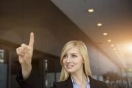 Young businesswoman signaling with finger in office - ISF16545