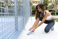 Sportive young woman tying her shoes before workout - KKAF01153