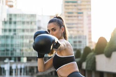 Portrait of sportive young woman boxing in the city - KKAF01156