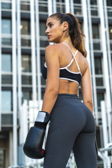 Sportive young woman with boxing gloves in the city in front of a high-rise building - KKAF01174