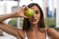 Portrait of attractive young woman holding an apple - KKAF01195