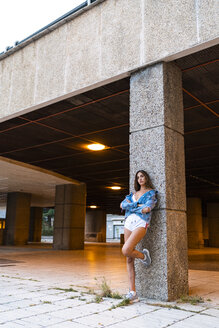 Attractive young woman in sportswear and denim jacket leaning against a column - KKAF01201