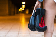Close-up of woman holding boxing gloves at illuminated underpass - KKAF01204
