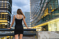 Rear view of young woman wearing black dress in the city at dusk - KKAF01210