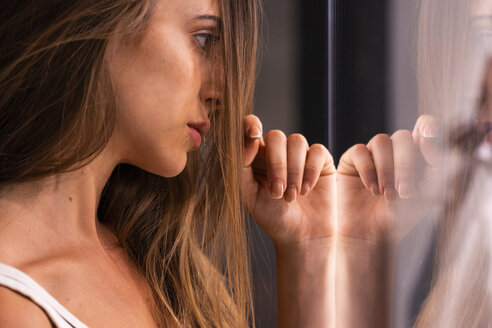 Serious attractive young woman leaning against glass pane - KKAF01213