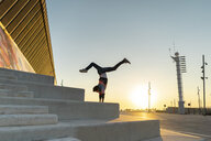 Acrobat doing handstand on stairs at sunrise - AFVF00664