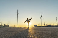 Acrobat doing movement training in city at sunrise - AFVF00667