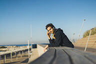 Man with headphones leaning on parapet, looking at view - AFVF00688