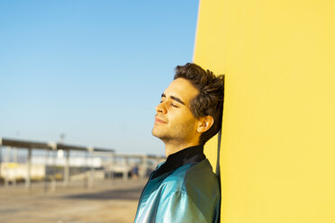 Man leaning against yellow wall, relaxing with eyes closed - AFVF00694
