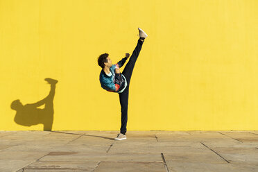 Acrobat doing movement training in front of a yellow wall - AFVF00697