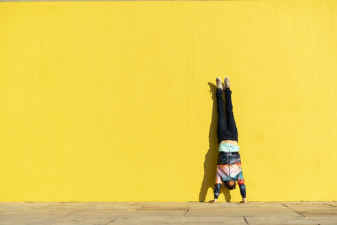 Acrobat doing handstand in front of a yellow wall - AFVF00700