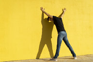 Man standing with hands on yellow wall, rear view - AFVF00706